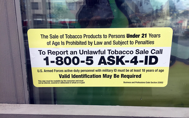 A sign at a gas station in California details the state's new law that raised the smoking age to 21. (Photo by Hipple Patel/Cronkite News)