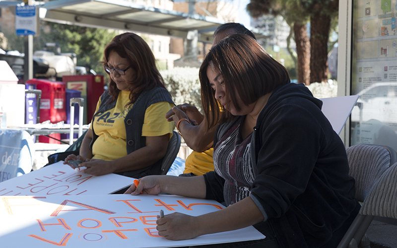 Elvira Guadarrama (left), Gustavo Cruz and Irma Gaytan make signs at a vigil in Phoenix against Latino voter suppression in the 2016 election on Nov. 7, 2016.  (Photo by Courtney Columbus/Cronkite News)