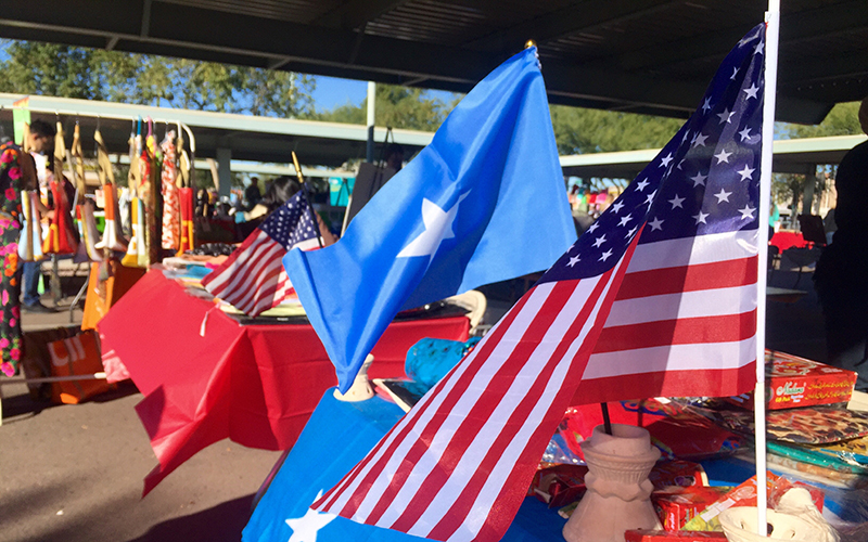 American and Somalian flags decorate a booth at the Fall 2016 World Bazaar and Phoenix Community Market event on Dec. 3, 2016 (Photo by Danielle Quijada/Cronkite News)