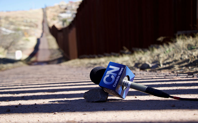 A detailed view of the Cronkite News logo with the U.S.-Mexico border wall in the background in Nogales, Arizona, on Wednesday, January 25, 2017. (Photo by Taylor Rearick/Cronkite News)