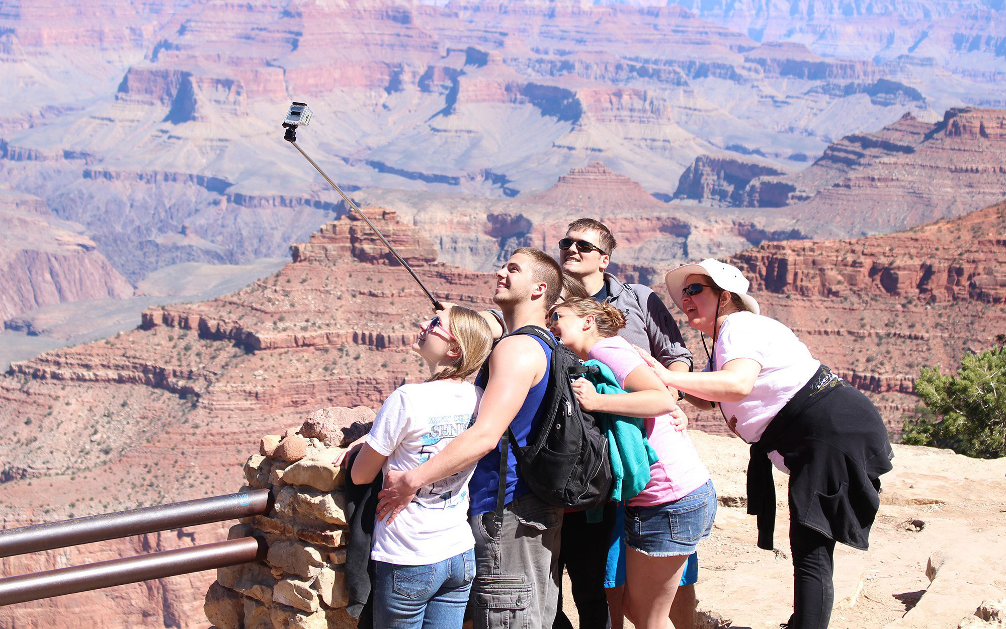 Tourists pose for a selfie in Grand Canyon National Park. (Photo by Sophia Kunthara/Cronkite News)