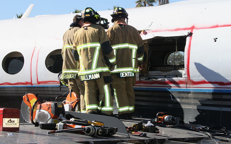 Mesa firefighers used a saw and other tools to cut makeshift emergency exits in a jet. (Photo by Alyssa Hesketh/Cronkite News)