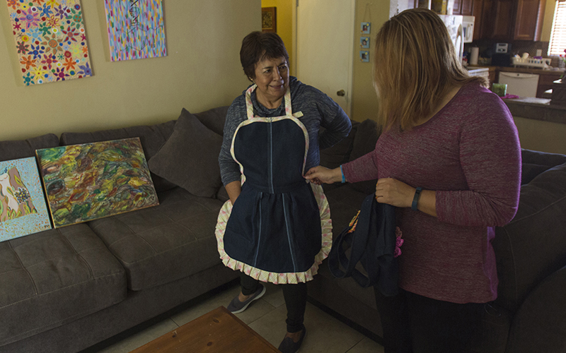Corina Villalobos wears a homemade apron at her daughter Ruby Rendon's home. Rendon cares for her mother, who has Parkinson's disease. Rendon picks up fabric at thrift stores for Villalobos, who keeps her hands mobile by sewing aprons at home. (Photo by Blake Hemmel/Cronkite News)