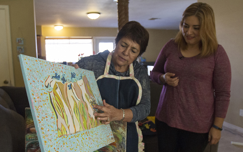 Corina Villalobos shows a painting of women to her daughter, Ruby Rendon. Villalobos has Parkinson's disease, and spontaneously paints whatever comes to her mind. (Photo by Blake Hemmel/Cronkite News)