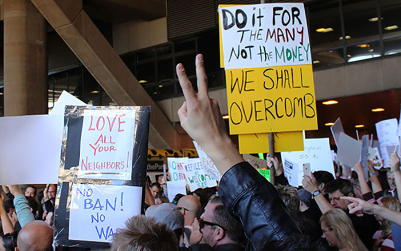 Hands displaying the peace sign fill the air during a rally for refugees at Phoenix Sky Harbor's Terminal 4, Sunday, January 29, 2017. (Photo by Tea Francesca Price/Cronkite News)