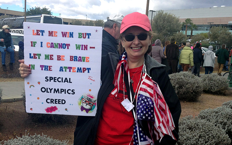 Former special education teacher Elizabeth Holmes, 54, holds a poster to showcase Special Oolympic students. (Photo by Saundra Wilson/Cronkite News)
