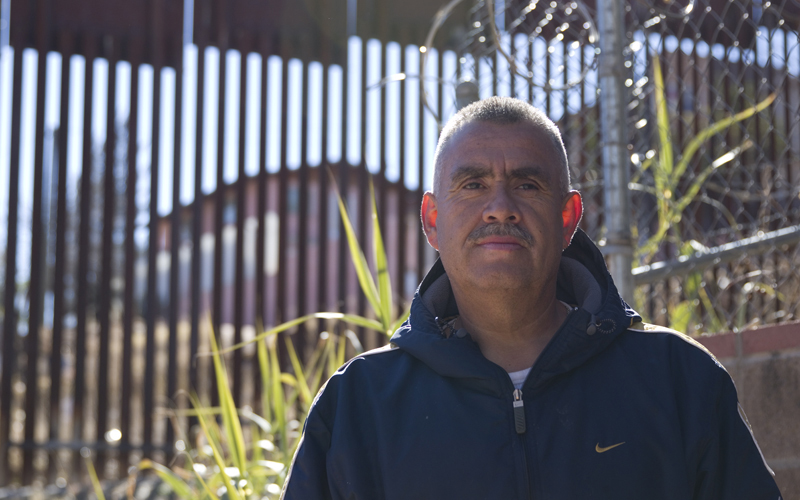 Carlos Santa Cruz, a landscaper who lives near the wall in Nogales, AZ, stands in front of the border wall in Nogales on January 25, 2016. (Photo by Josh Orcutt/Cronkite News)