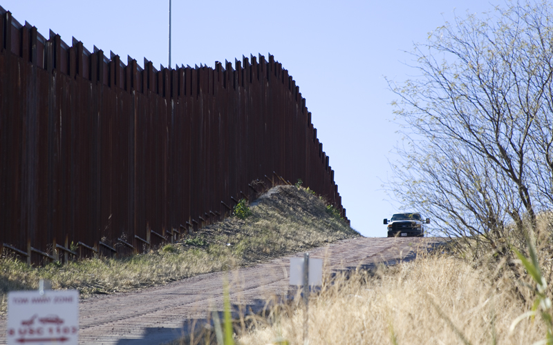 A Border Patrol agent in his truck looks over the current border wall between the United States and Mexico in Nogales on Wednesday, January 25, 2017. (Photo by Josh Orcutt/Cronkite News)
