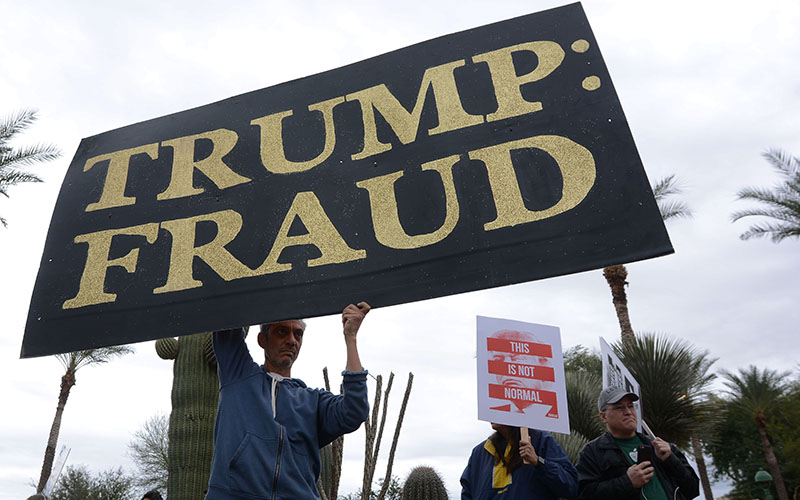 "Phoenix resident Chris Fleischman, 54, stands with a large sign that reads ""TRUMP: FRAUD"" in front of the Arizona State Capitol on Friday, January 20, 2017. The gathering was in protest of the inauguration of President Donald Trump. (Photo by Ryan Santistevan/Cronkite News)"