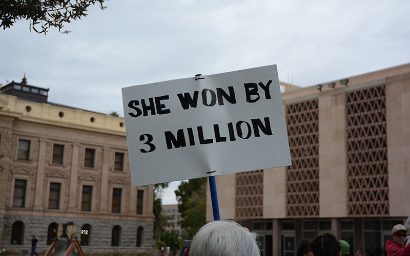 "One woman held a sign that read ""SHE WON BY 3 MILLION,"" referring to the presidential popular vote victory by Trump's Democratic opponent Hillary Clinton (Photo by Ryan Santistevan/Cronkite News)"