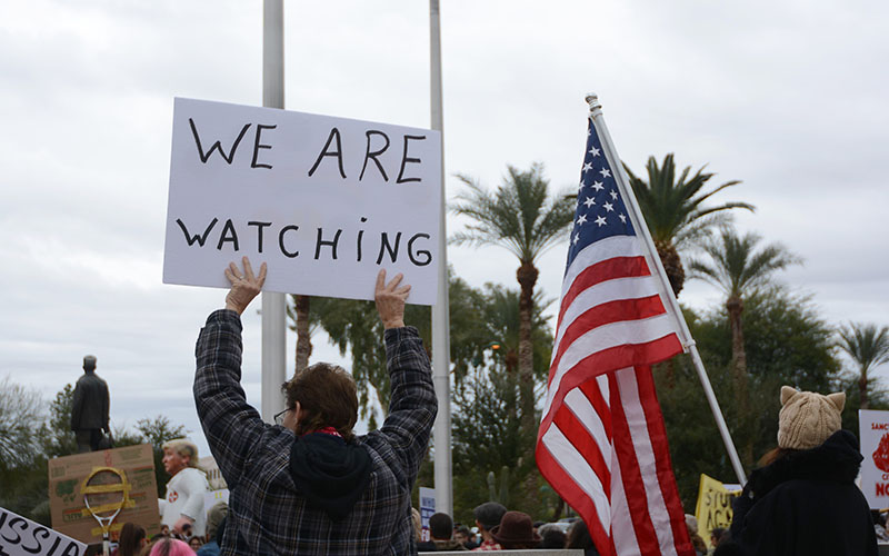 "One protester held handmade sign that read ""WE ARE WATCHING."" (Photo by Ryan Santistevan/Cronkite News)"