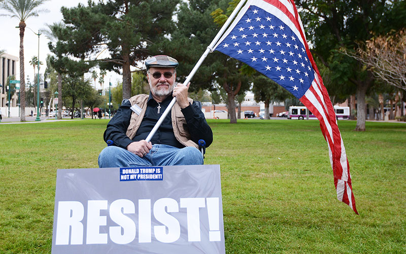 Maricopa resident Dennis Howerton, 67, said he has friends in the LGBT community and in communities of color who fear what will happen during the Trump administration. Howerton joined the President Trump inauguration protest in front of the Arizona State Capitol on Friday, Jan. 20, 2017. (Photo by Ryan Santistevan/Cronkite News)
