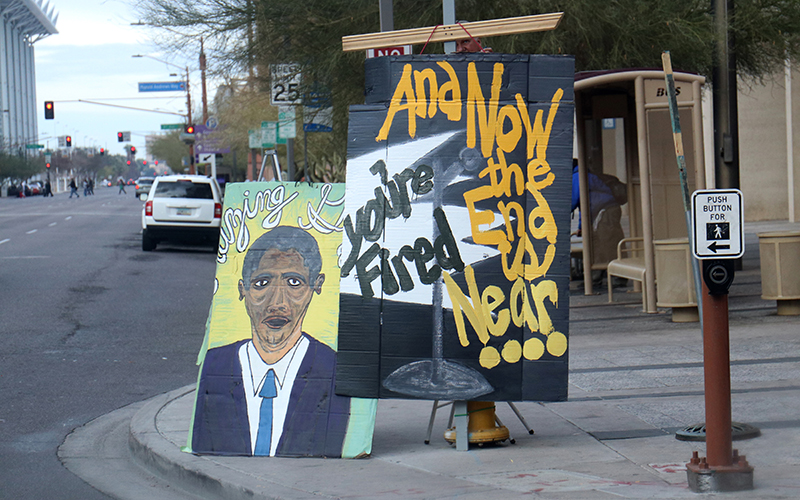 A protester on the corner of 1st Avenue and Washington Street in Phoenix displayed signs with anti-Trump sentiments. The signs were two of many used in protest of Trump's inauguration on Jan. 20, 2017. (Photo by Nicole Tyau/Cronkite News)