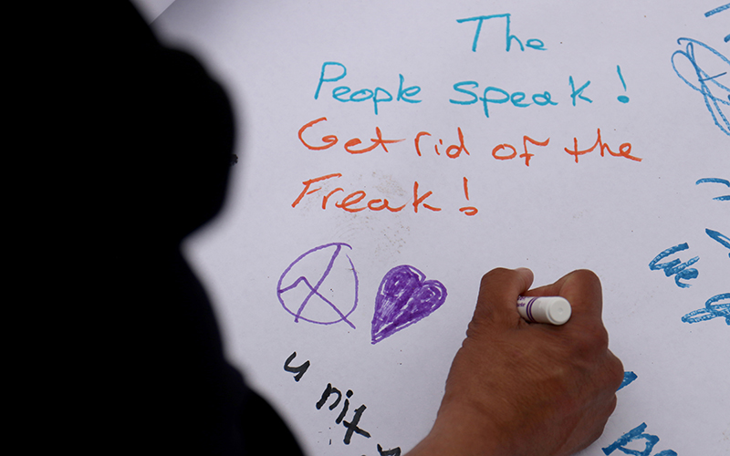 One protester draws a peace sign and a heart as a contribution to the hand-made poster. The sign was an activity for people at the inauguration protest at the Arizona State Capitol on Jan. 20, 2017. (Photo by Nicole Tyau/Cronkite News)