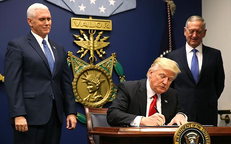 Vice President Mike Pence, left, and Defense Secretary James Mattis look on Friday as President Donald Trump signs an executive order suspending refugee admissions to the U.S. (Photo by Carlos Barria/Reuters)
