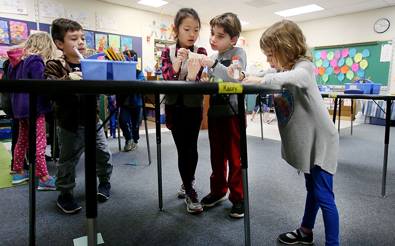 Table mates (from left) Julian Hopkins, 6, Elise Kim, 7, Sawyer Lazarus, 8, and Lexi Appel, 7, work on their group project at a standing desk in Tiffany Wiley's multi-grade elementary class at Manzanita Elementary School in Tucson. The school is experimenting with the idea of standing desks, implementing the change in January. (Photo courtesy of Mike Christy/Arizona Daily Star)© 2017 Arizona Daily Star