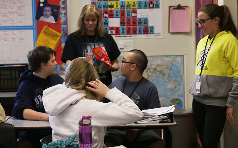 Teacher Heather Robinson hands out less-desirable lollipops to students Caleb Kaufman, Brandon Barnes and Mackenzie Leblanc (seated, left to right) during an exercise to teach her students about segregation. (Photo by Kaddie Stephens/Cronkite News)