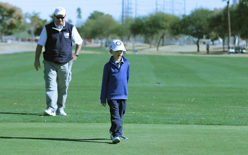 Easton Reischl, 6, is followed by his father and caddie Phil Reischl during a U.S. Kids Golf event at Ken McDonald Golf Course in Tempe. (Photo by Tyler Handlan/Cronkite News)