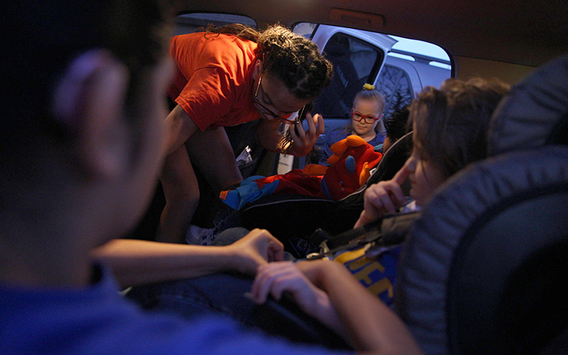 The older children help strap the younger children into their car seats as they prepare to leave for school on Friday, Feb. 10, 2017. (Photo by Johanna Huckeba/Cronkite News)