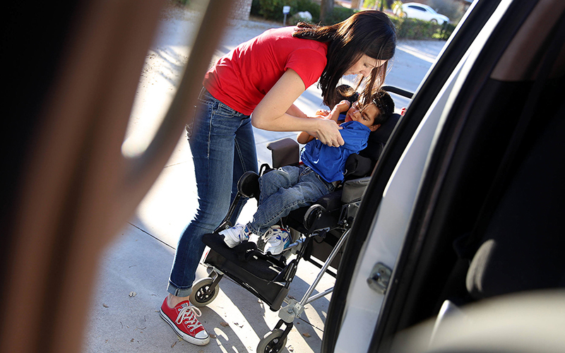 Jessika Reed transfers Zealynd, her 5-year-old adopted son with cerebral palsy, from the car to attend school on Friday, Feb. 10, 2017. (Photo by Johanna Huckeba/Cronkite News)