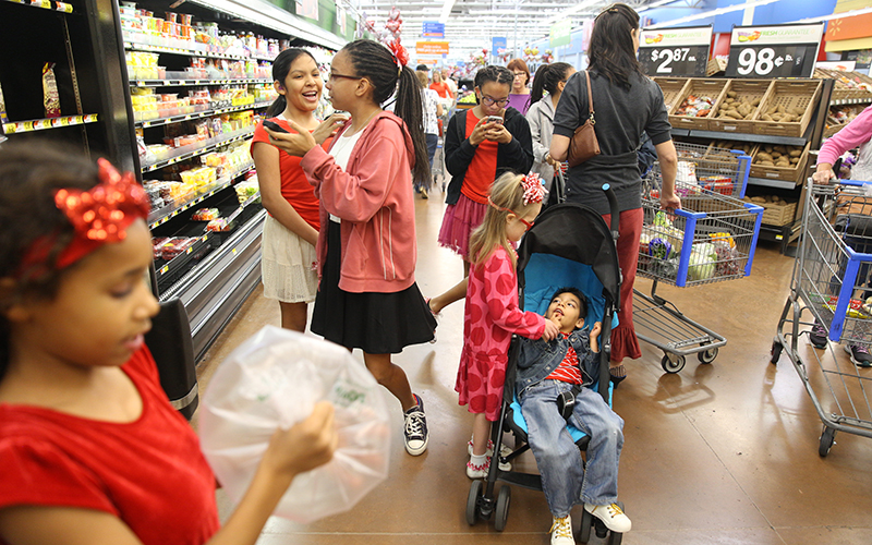 The Reed family shops for groceries after church on Sunday, Feb. 12, 2017. Feeding so many mouths adds up quickly, so fitting within a food budget is a challenge. Jessika's main source of income comes from the state, which compensates her for the care she is providing to her kids with special needs who were previously in the foster care system. (Photo by Johanna Huckeba/Cronkite News)