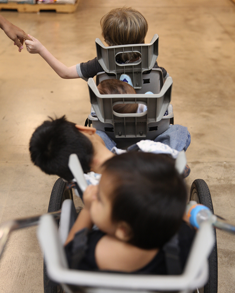 "Fynnland sits at the front of the quad stroller holding his older sister's hand during a shopping trip on Nov. 2, 2016. Behind Fynn is Jayden, Zealynd, and Ched or ""Little Bear,"" a foster child temporarily placed in Jessika's care.(Photo by Johanna Huckeba/Cronkite News)"