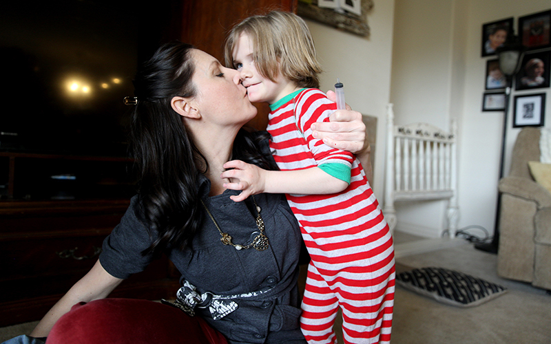 Jessika kisses her son Fynn after his afternoon nap on Sunday, Feb. 12, 2017. Diagnosed with cerebral palsy, Jessika said that doctors believed that Fynn would never walk, communicate or function above the motor skills of an infant. Fynn does not communicate verbally currently, although he did for a time, but he communicates with sign language and is as mobile as any 7-year-old. (Photo by Johanna Huckeba/Cronkite News)