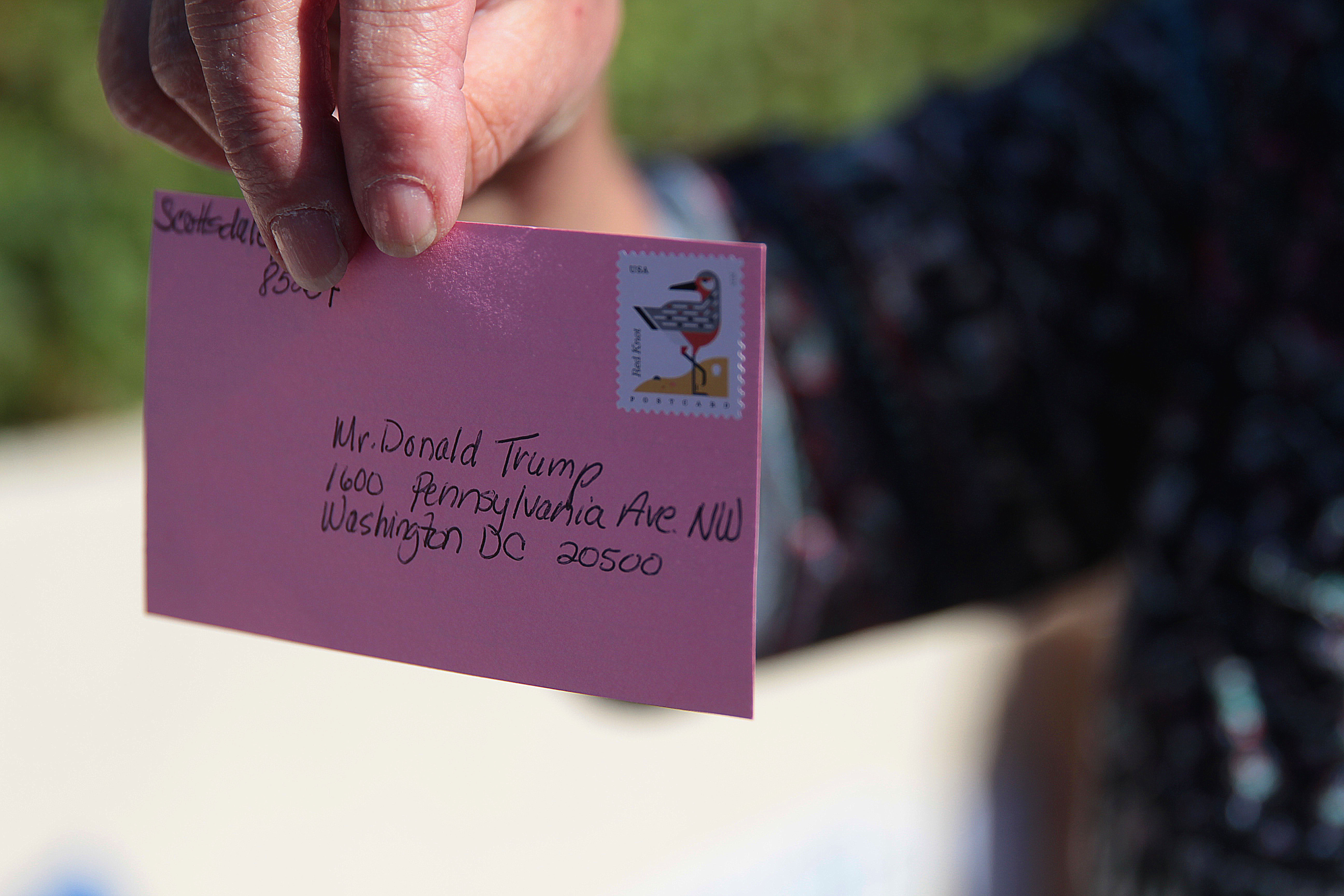The Puente Human Rights Movement is encouraging people to send pink postcards to the White House as a sign of protest. Representatives from Puente hand out cards at an anti-Trump protest outside Sen. Jeff Flake's office on February 7, 2017 in central Phoenix. (Photo taken by Taryn Martin/Cronkite News)