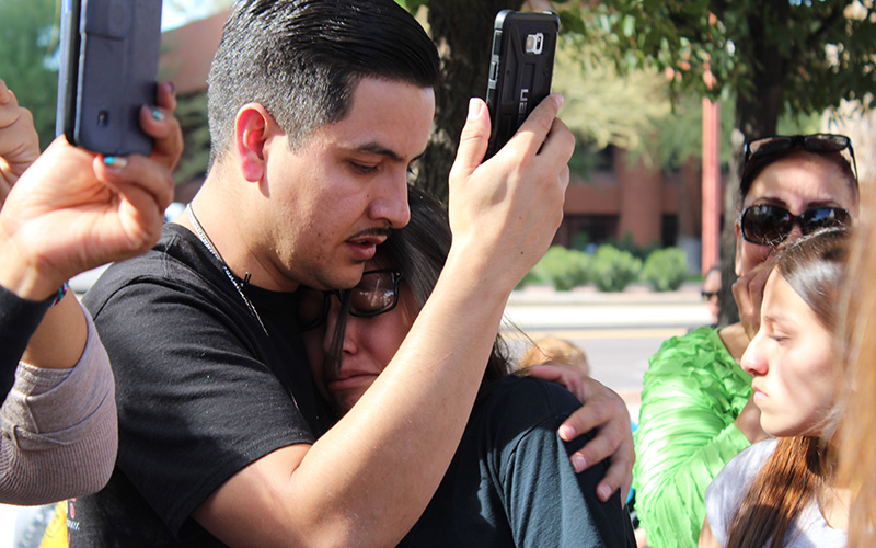 Aarón Rayos and his daughter, Jacqueline, 14, comfort each other after hearing from Guadalupe Garcia De Rayos' immigration attorney that she was arrested by ICE. (Photo by Charlene Santiago/Cronkite News)