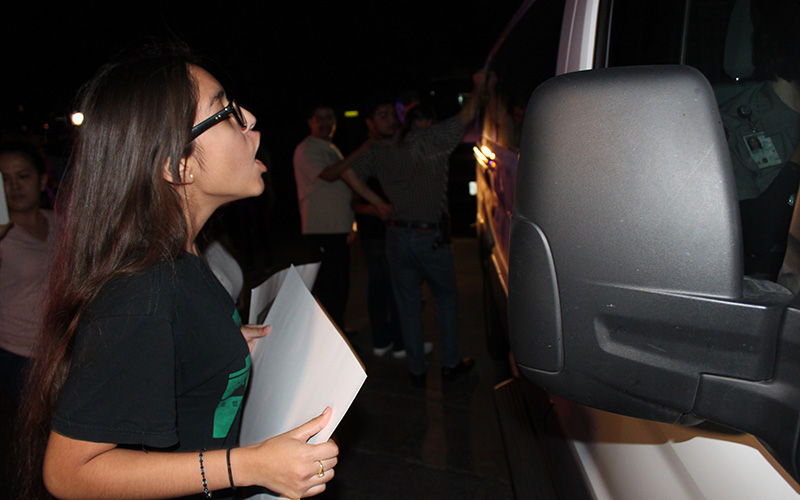 Jacqueline Rayos, 14, yells at ICE officers as they drive away with her mother and other immigrants who were detained. (Photo by Charlene Santiago/Cronkite News)