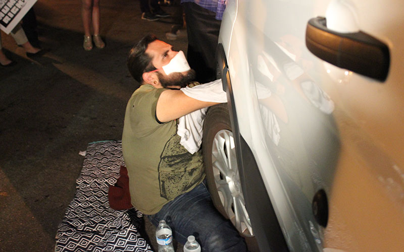 Manuel Saldaña, a military veteran who among protesters, stops, the ICE vehicle from taking Guadalupe Garcia De Rayos after she's detained.  (Photo by Charlene Santiago/Cronkite News)