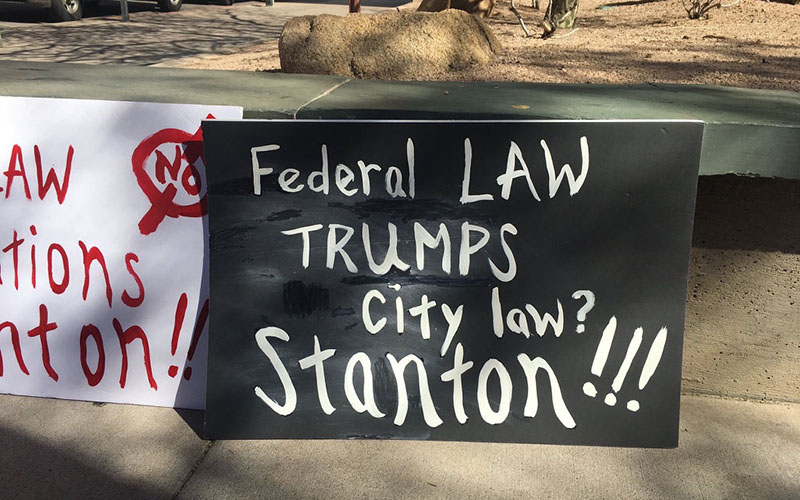 Opponents display signs outside a Phoenix City Council meeting deciding whether Phoenix should declare itself a sanctuary city for immigrants and refugees. (Photo by Sarah Jarvis/Cronkite News)