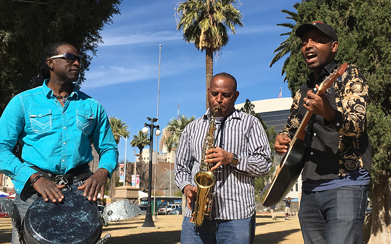 Richard Noel, CEO of Jam2Grow, plays drums while refugees Tilahun Liben of Ethiopia and Jean Marie Menutore of Burundi play instruments from their African countries to create a unique blend of music. (Photo by Mindy Riesenberg/Cronkite News)