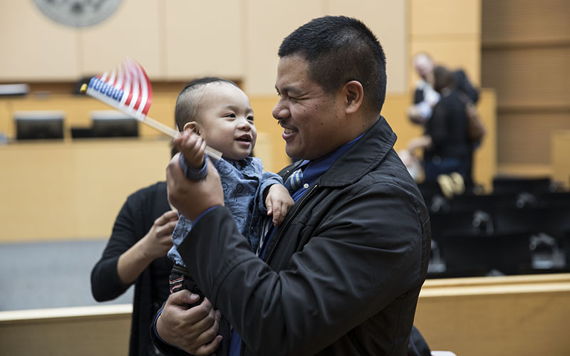 Jonathon Matabang holds his son Jacob after the naturalization ceremony of his wife, Cheryl, who immigrated from the Phillipines. (Photo by Johanna Huckeba/Cronkite News)