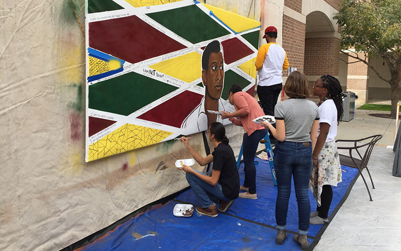Volunteers help Trent put the finishing touches on the mural on the last live-painting day. (Photo by Jared McDonald/Cronkite News)