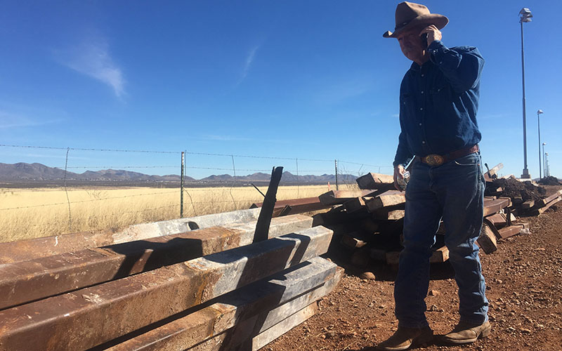 John Ladd talks on the phone with a fellow rancher as he walks on his property near construction material that is being used to upgrade the current border fence.