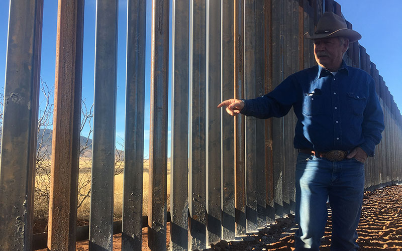 John Ladd stands near the border fence located on his ranch in Arizona.