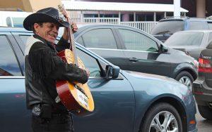 "José Guadalupe Esquer Barrera, ""El Bronco Negro de la Sierra,"" plays and sings in the border crossing line in Nogales, Mexico. (Photo by Charlene Santiago/Cronkite News)"