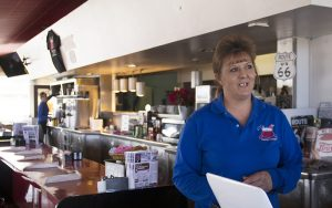 Tammy Rutherford stands in the diner she owns on Route 66 in Kingman, Arizona. A Trump voter, she said he is