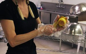Taryn MacQuilkin, owner of The Muffin Girl, unwraps a muffin at her bakery in Mesa. She started out by baking muffins at home. (Photo by Janie Hoyt/Cronkite News)