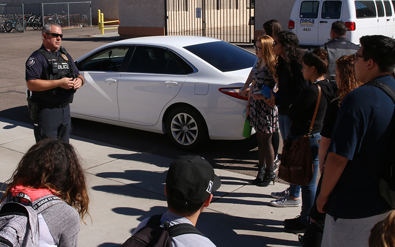 Ryan Lovell, a Mesa police officer, gives tips to high school students at Mountain View High School in Mesa about what to do when pulled over by a police officer. (Photo by Blake Hemmel/Cronkite News)