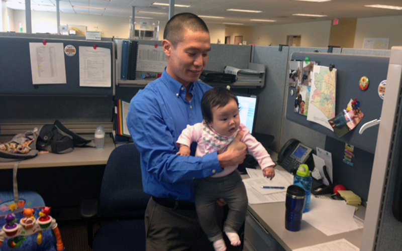 State employee Kevin Watanabe has a stroller, car seat and playmat for his daughter Katelyn in his cubicle. (Photo by Saundra Wilson/Cronkite News)