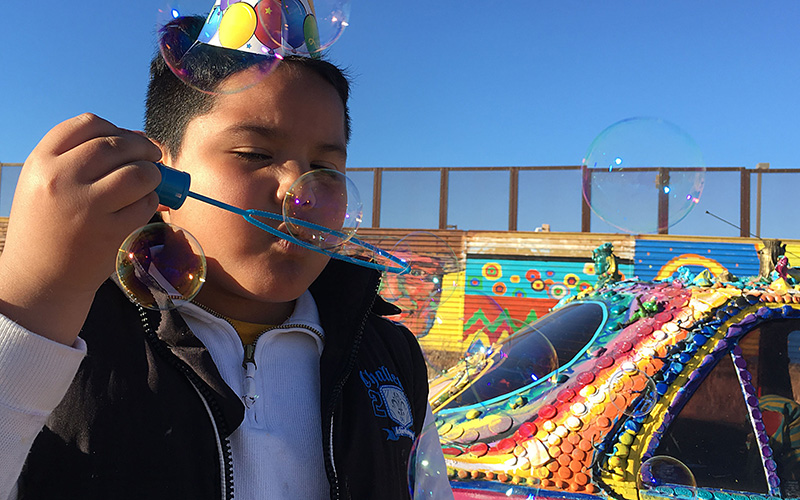 A child at a farewell party for a mural on the border fence in Naco, Sonora. Construction crews will demolish the fence to make way for a new barrier. (Photo by Charlene Santiago/Cronkite News)