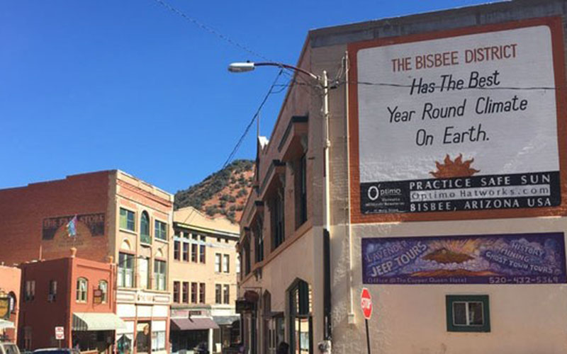 "Bisbee's iconic saying, ""The Bisbee District Has the Best Year Round Climate On Earth,"" is written on the side a building along Main Street. That may be true, given the clear skies and 65-degree weather the town regularly experiences. (Photo by Diego Mendoza-Moyers/Cronkite News)"