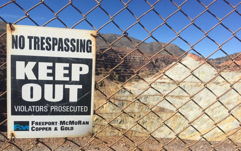 "A ""no trespassing"" sign gets the message across, attached to barbed-wire fencing outside of the now-defunct Copper Queen Mine. The mine propelled Bisbee to regional economic prosperity, until its closing in 1985. (Photo by Diego Mendoza-Moyers/Cronkite news)"