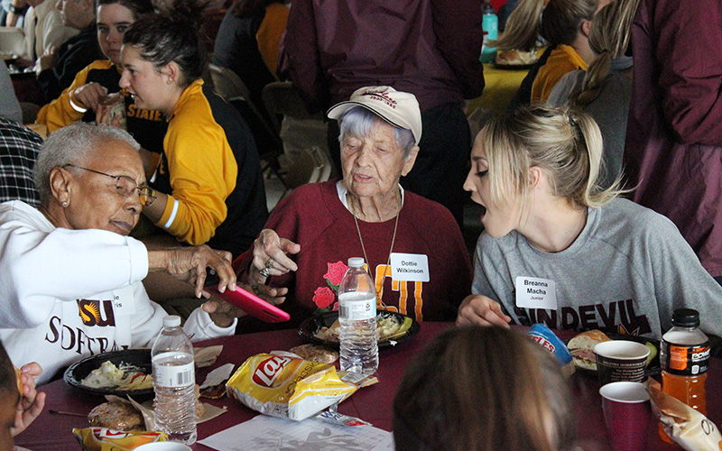 Billie Harris (left), Dottie Wilkinson (center) and ASU pitcher Breanna Macha (right) look at old photos during the ASU softball team's lunch with former softball players. Harris is the first African-American woman inducted into the Amateur Softball Association of America Hall of Fame, while Wilkinson is not only a member of the National Softball Hall of Fame, but also the Women's International Bowling Congress Hall of Fame. (Photo by Tyler Drake/ Cronkite News)