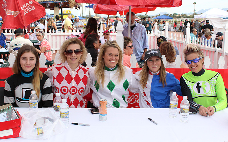 Turf Paradise jockeys, from left to right, Amelia Hauschild, Vanessa Romberg, Janine Smith, Natasha Coddington, Aubrie Green all take a break from signing autographs at Turf Paradise on Saturday, Feb. 11, 2017 in Phoenix. (Photo by Samantha Pell/Cronkite News)