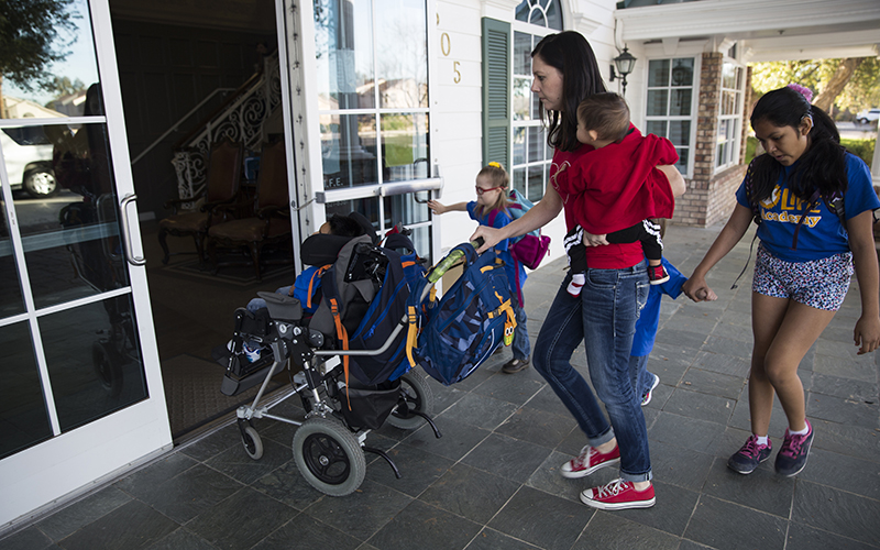 Parys, 12, holds the door for her family as they enter Lauren's Institute for Education where four of children who have special needs go to school. Cassara, far right, holds Fynn's hand as they walk behind their mom who is carrying Jayden and pushing Zealynd in the stroller. (Photo by Johanna Huckeba/Cronkite News)