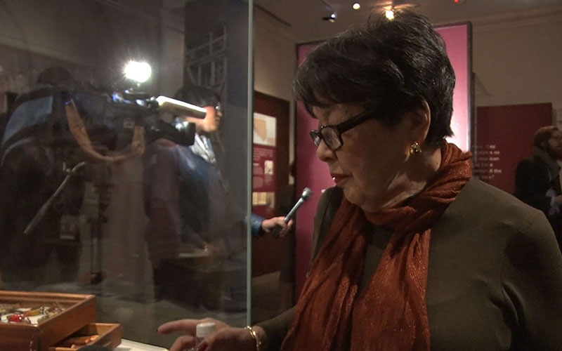 Mitzi Oka McCullough looks at an exhibit displaying birds carved by her father during the time their family was held in an internment camp for Japanese Americans during World War II. (Photo by Anthony Marroquin/Cronkite News)