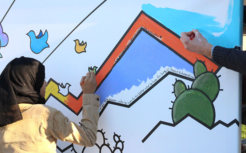 Painters are encouraged to write their prayers or messages of peace and love on the canvas, so that their thoughts always stay with the mural, at the Painting for Peace community mural day in downtown Phoenix. (Photo by Rachael Bouley/Cronkite News)